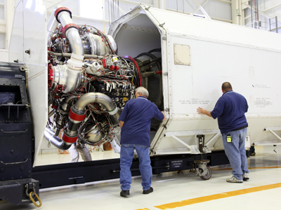 Technicians oversee the installation of a Pratt & Whitney Rocketdyne RS-25D engine into a transportation canister Jan. 12 in the Engine Processing Facility at Kennedy.