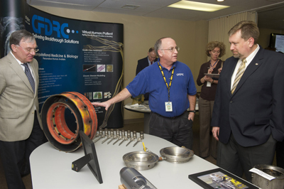 NASA Chief Technologist Dr. Mason Peck, right, visiting Huntsville from NASA Headquarters, is being briefed on some of CFD Research Corp.'s newest technologies from the firm�s Matthew Thomas, center, vice president of propulsion and power; and Dr. Andrzej Przekwas, chief technology officer.