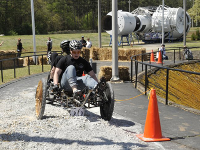 A team from the Rhode Island School of Design in Providence pedals through a bumpy patch of the course at the 2010 NASA Great Moonbuggy Race. The school will join some 100 returning and rookie student teams at this year's competition.