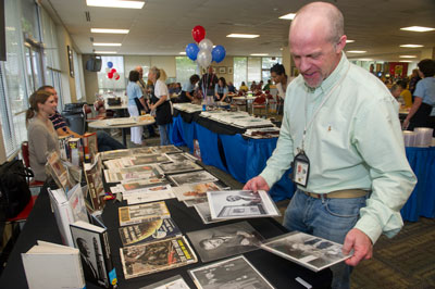 Chip Moore, a mechanical engineer of the Engineering Directorate, looks through pictures of von Braun. Exhibits and photo displays were set up in the Building 4203 cafeteria, recounting the historic work of von Braun and his team to launch the first American explorers into space and to the moon.