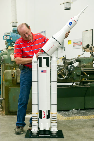 Barry Howell, a model maker supporting the Office of Strategic Analysis & Communications, adds the top portion of a new 6-foot-5-inch, 1:50-scale Space Launch System model created in the Marshall Space Flight Center's model shop in Building 4631.