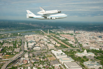 Space shuttle Discovery, mounted atop a NASA 747 Shuttle Carrier Aircraft, was photographed from a NASA T-38 aircraft as it flew over the Washington skyline.