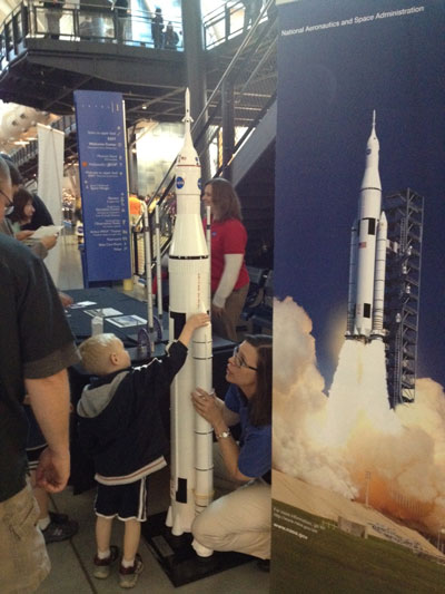 A young explorer gets a hands-on description of NASA's Space Launch System at the space shuttle Discovery delivery celebration April 19 at the Smithsonian's Udvar-Hazy Center from Twila Schneider, an SLS communications coordinator supporting Marshall's Office of Strategic Analysis & Communications.