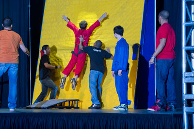 Huntsville Middle School student Patrick Fair, in the red jumpsuit, demonstrates Newton's first law of motion by jumping onto a velcro wall and remaining there until he is pulled off, at FMA Live! during the National Take Our Children to Work Day on April 26.
