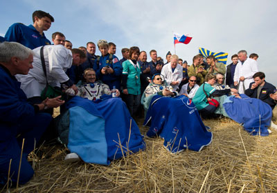 Expedition 30 Commander Dan Burbank, left, and Flight Engineers Anton Shkaplerov, center, and Anatoly Ivanishin, sit in chairs outside the Soyuz capsule just minutes after they landed in a remote area outside the town of Arkalyk, Kazakhstan, on April 27.