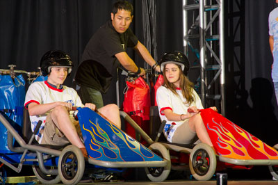 At FMA Live!, two children from Huntsville city schools race dragster go-carts propelled by air pressure across the stage to illustrate Newton's third law: For every action, there is an equal and opposite reaction.