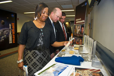 Visitors examine various NASA display items in the exhibits area at the State House in Montgomery on May 3.