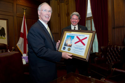 Alabama Gov. Robert Bentley is presented an Alabama state flag that was flown aboard space shuttle Discovery in February 2011 by Acting Marshall Center Director Gene Goldman during NASA Day in Alabama on May 3.