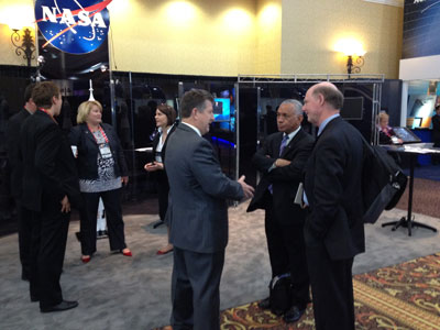 NASA Administrator Charles Bolden, in the center foreground, talks with participants visiting the OneNASA exhibit at 28th annual National Space Symposium.