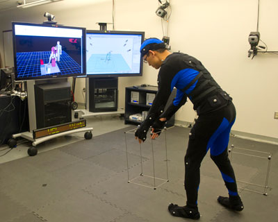 Marshall engineer Peter Ma, in the Marshall Virtual Environment Laboratory, wears a suit covered with spherical reflectors that enable his body positions to be captured by a motion-tracking system.