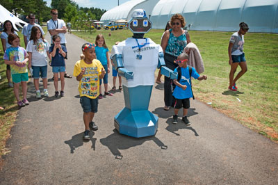 A group of excited children -- and a few adults, too -- gather around for a little meet-and-greet with picnic newcomer Oscar the Robot.