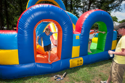Children make their way through one of the picnic's many inflatables.