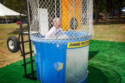 Stephen Doering, director of Marshall's Office of Center Operations, goes down with a splash at the dunking booth. The dunking booth was just one of a host of games and activities at the picnic, including water slides and inflatables.