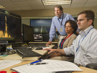 Paul Doyle, right, Yvette Binford, center, and Ken King integrate and debug the SLS avionics software.