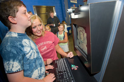 Allison Young, center in pink shirt, a Wyle Corp. employee supporting Marshall's Space Launch System Program Office, helps an excited youngster take a souvenir astronaut photo at one of the NASA photo kiosks during