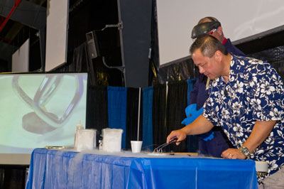 Marshall engineer Howard Soohoo, right, and electronics technician Chris Conn, partially hidden, both supporting Marshall's Engineering Directorate, show how to freeze objects with liquid nitrogen to children and their parents during Marshall's annual