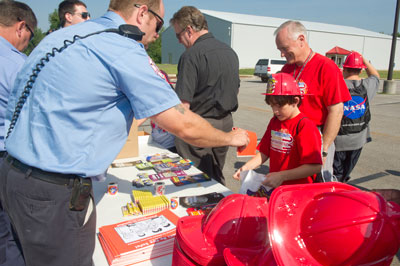 Eight-year-old Jackson Moore gets a few goodies to take home from a Redstone Arsenal fireman. Looking over Jackson's shoulder is his grandfather, David Guy, a safety and occupational health specialist supporting Marshall's Safety & Quality Department.