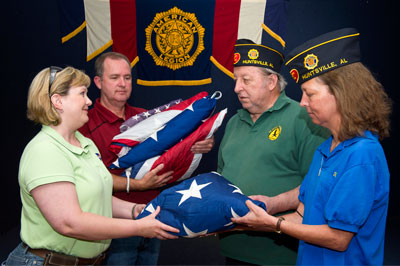 From left, Philisha Stephens, property disposal officer, and Greg Tate, senior property disposal specialist, both of Marshall's Property Management Office in the Office of Center Operations, hand over five American flags to Ted Lott and Ranae Emmett of the American Legion for proper retirement.