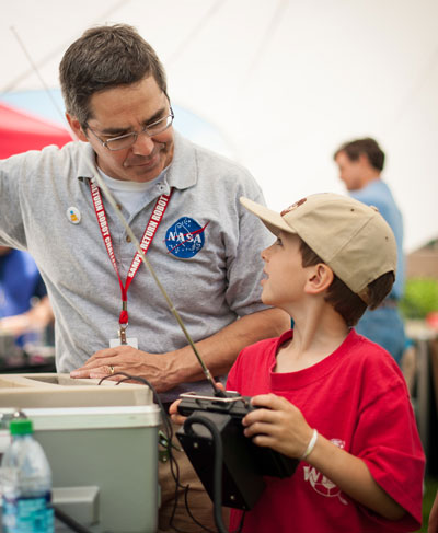 Centennial Challenges Program Manager Sam Ortega of the Marshall Center teaches a young attendee how to work the Be A Bot controller at the TouchTomorrow festival at the Worcester Polytechnic Institute. Ortega has headed the Centennial Challenges Program since September 2011.