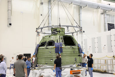 The Orion crew module is lowered onto a workstand in the Operations and Checkout Building high bay at the Kennedy Space Center.