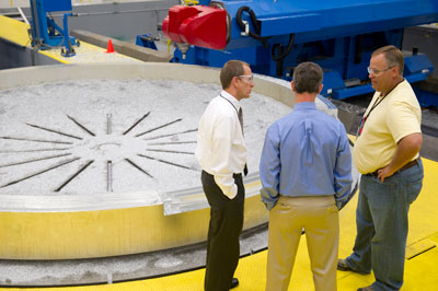 Three members of the Space Launch System team discuss the machining of an aluminum adapter ring similar to the design needed for Exploration Flight Test-1 at the Marshall Space Flight Center in Building 4705.
