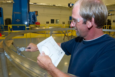 David Osborne, a machinist with the Space Systems Department - Mechanical Fabrication Branch at Marshall, takes measurements on a prototype aluminum ring, which shares the design of adapter rings to be used on the first flight test of the Orion spacecraft in 2014.
