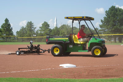 Jay Hollenbeck, a mechanical engineer in the Facilities Management Office and the field maintenance manager for the MARS Softball Club, prepares the field for the next game using the new Solar Gator Groomer. A legacy Saturn-1B can be seen in the background.