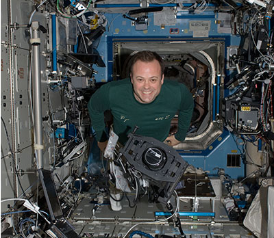Astronaut Ron Garan works with the International Space Station Agricultural Camera (ISSAC) in the Destiny laboratory of the International Space Station. The camera is used to take frequent images principally of vegetated areas such as growing crops, grasslands and forests.