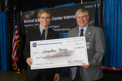 Jonathan Yancey, left, a chemical engineering student at West Virginia University in Morgantown, receives a check from Ron Wetmore, right, vice president of Lockheed Martin Space Systems Company.