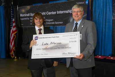 The first-place winner of the design category is Luke Peterson, left, an aerospace engineering student at Mississippi State University in Starkville, for his presentation on Coverage Analysis of the Wide Field X-ray Telescope. Wetmore, right, presents a check to Peterson.