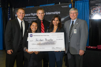 Placing first in the team category are, from left, Zachary Grunder, Megan Sung, Bryce Schaefer and Vanessa Dorado. Wetmore, right, presents a check to the students.