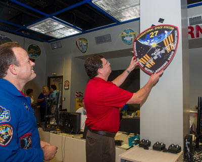 Mark Roberts, right, in NASA's Payload Operations Center at the Marshall Space Flight Center, hangs the Expedition 27 plaque in the control room in Building 4663. Expedition 27/28 astronaut Ron Garan, left, signed the plaque during his visit to Marshall on Aug. 7.