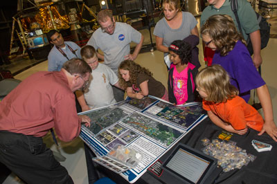 Dr. Steve Williams, left, planetary science division education/public outreach lead at NASA Headquarters, shows the group a poster about how far the Apollo astronauts and NASA's Spirit and Opportunity rovers might have roamed had they landed in a familiar place.