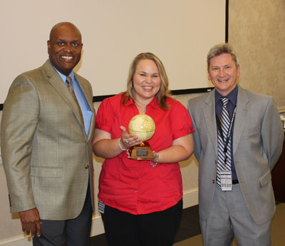 Amanda Holcomb, center, is presented with the 'Out of this World Award' for her exceptional dedication and superb work as administrative officer by OSAC Director Bobby Watkins, left, and Johnny Stephenson, OSAC deputy director.