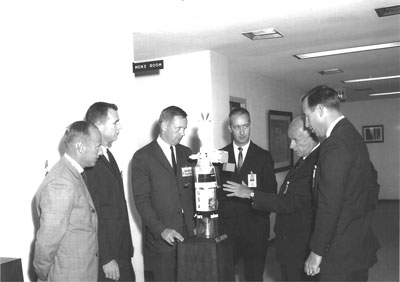 Former Marshall Space Flight Center Deputy Director Dr. Eberhard Rees, second from right, shows astronauts, from left, Charles Conrad Jr., David Scott, Neil Armstrong, James McDivitt and James Lovell, a model of a cluster of space experiments attached to an uprated Saturn I second stage in 1967.