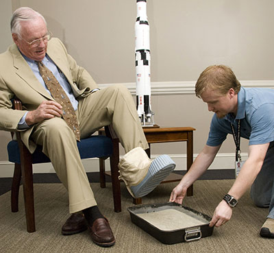 Neil Armstrong casts his astronaut bootprint during a visit to the Marshall Space Flight Center in 2007. Assisting Armstrong is Daniel McFall, a graphic designer for AI Signal Research Inc., supporting the Office of Strategic Analysis & Communications.