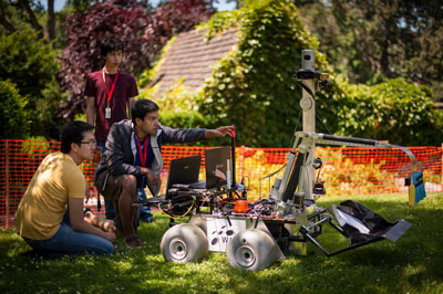 Teammates from the University of Waterloo in Canada work with their robot on the practice field at the Sample Return Robot Challenge at Worcester Polytechnic Institute in Worcester, Mass., in June.