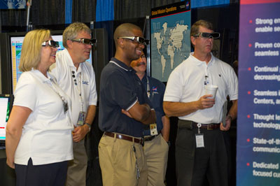 At the expo, Marshall Center team members watch a video highlighting NASA spaceflight and engineering capabilities in 3-D at Marshall's Mission Operations Laboratory booth. The video demonstrated the use of 3-D technology within NASA.