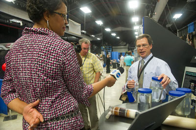 Angela Storey, left, a public affairs officer in the Office of Strategic Analysis & Communications, interviews engineer Jay Perry, right, who explains the Environmental Control and Life Support Systems, or ECLSS, work being conducted at the Marshall Center.