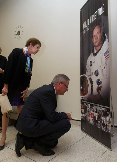 Hansen, right, and his wife, Peggy Hansen, look at pictures on a large banner in the Building 4200 lobby documenting Armstrong's NASA career.