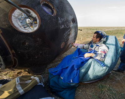 Expedition 32 NASA Flight Engineer Joe Acaba signs the side of his Soyuz spacecraft shortly after he landed with his crewmates, Expedition 32 Commander Gennady Padalka and Flight Engineer Sergei Revin of Russia, in a remote area near the town of Arkalyk, Kazakhstan, on Sept. 16.