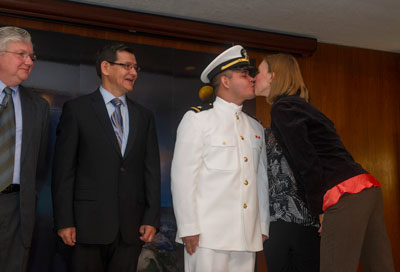 Marshall space systems engineer and U.S. Navy Ensign Hernando Gauto, center, receives a kiss from his wife Alisa during his Navy commissioning ceremony, held Sept. 18 in Building 4200, Morris Auditorium. Gauto's father, Eleuterio Gauto, left, looks on.