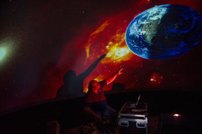 Left, Dr. Bill Cooke takes visitors on a tour of the solar system in one of two inflatable planetariums at the event during the third annual