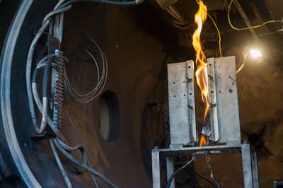 During a combustion demonstration test, a sample material is set on fire for 30 seconds in a large chamber, filled with varying pressure levels of nitrogen and oxygen.