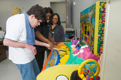 Sonya Dillard, right, an industrial safety engineer in Marshall's Safety & Mission Assurance Directorate, looks on as an Ability Plus resident -- aided by an Ability Plus staff member -- plays a game in the facility's entertainment room.
