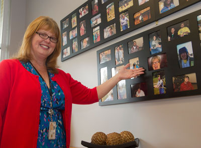 Lisa Carr, technical assistant to the chief of Marshall's Systems Engineering Division, part of the Vehicle & Spacecraft Systems Department, proudly shows off a picture of her sister, Tonya Hawkins, in the lobby of Ability Plus in Madison. Hawkins has been a resident at the facility since 2007.