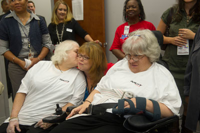 While on a tour of Ability Plus, Lisa Carr, center, gets a kiss on the cheek from the former roommate of her sister, Tonya Hawkins, right. Hawkins and the roommate are close friends, participating together in activities at the facility.