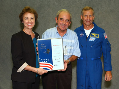 Marshall photographer Emmett Given, center, is presented the Silver Snoopy by STS-111 Commander Kenneth Cockrell, right. With Given is his friend, Linda Riley.