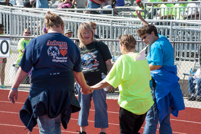 Debbie Allen, center in background, a human resources specialist in Marshall's Human Resources Services Office, cheers on a Special Olympics athlete as she -- with support from her family -- makes her way around the track.