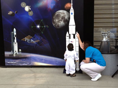 A tiny visitor to the California Science Center in Los Angeles dreams big during the space shuttle Endeavour celebration Oct. 30-Nov. 4 as Twila Schneider, right, a communications strategist with ASI, shows him a scale model of the proposed SLS.